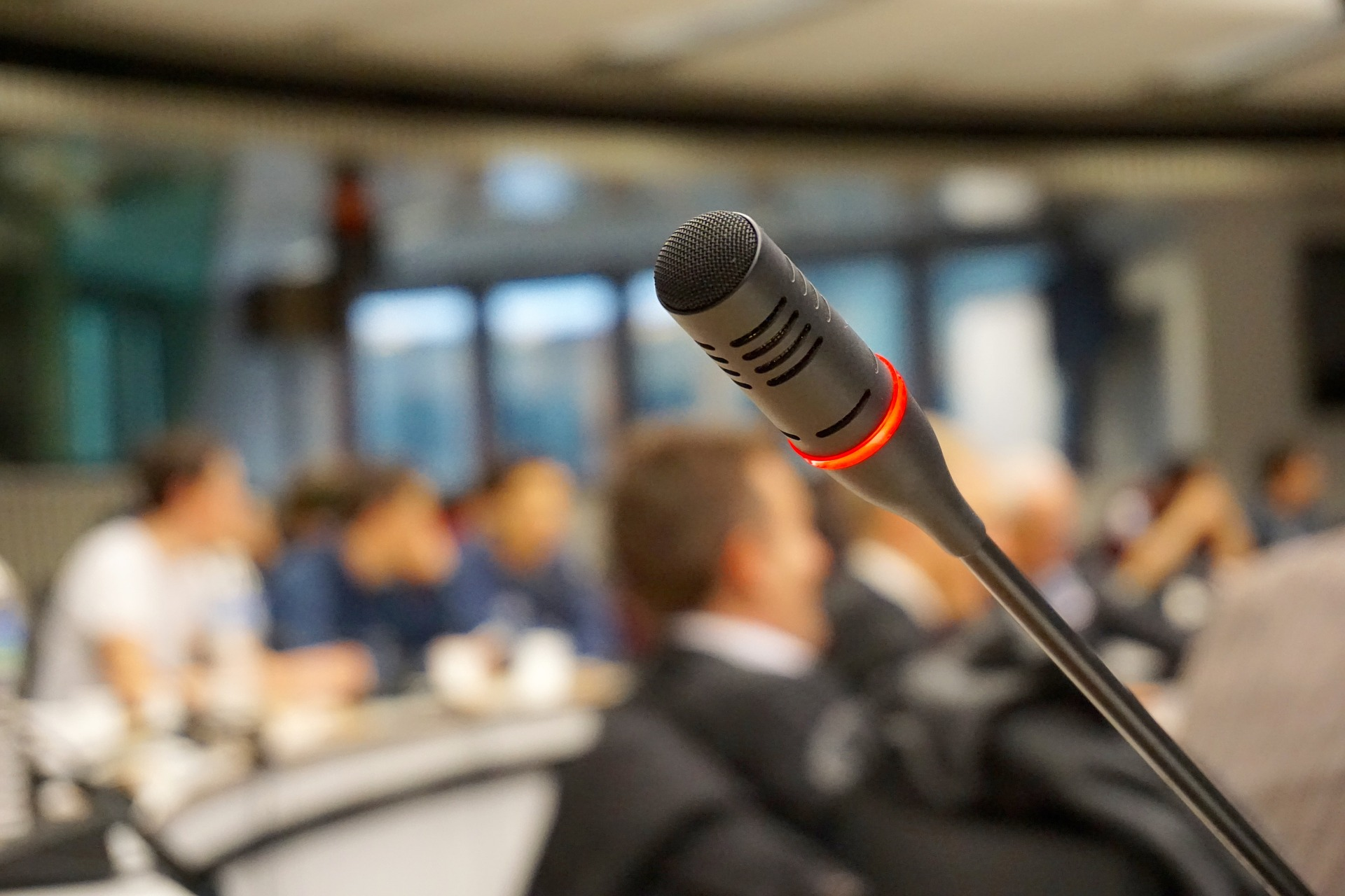 A conference room filled with people and focus on a microphone